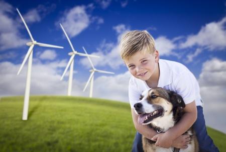 molino: Joven guapo azul ojos de niño y perro jugando cerca de turbinas eólicas y campo de hierba. Foto de archivo
