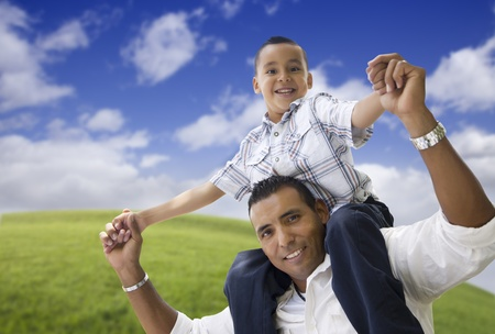 kinship: Hispanic Father and Son Having Fun Together in the Park.