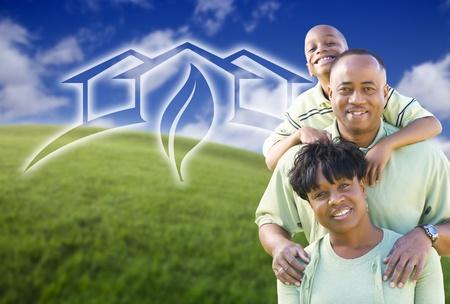 eficiencia: Feliz familia afroamericana y gráfico de casa verde en campo de hierba. Foto de archivo