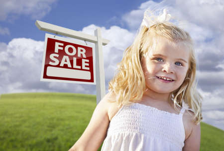 sales person: Adorable Smiling Girl in Grass Field with For Sale Real Estate Sign Behind Her.