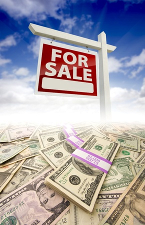 property for sale: Stacks of Money Fading Off and For Sale Real Estate Sign Against Blue Sky with Clouds.