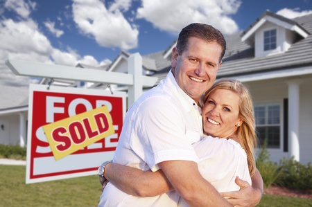 Happy Couple Hugging in Front of Sold Real Estate Sign and House. photo