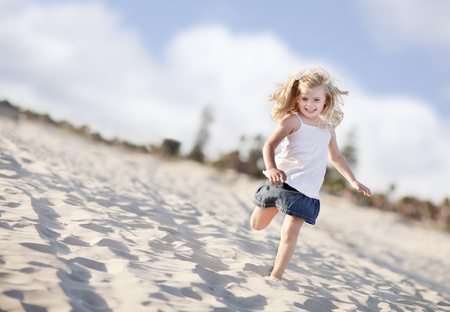 Adorable Little Girl Having Fun at the Beach One Sunny Afternoon. photo