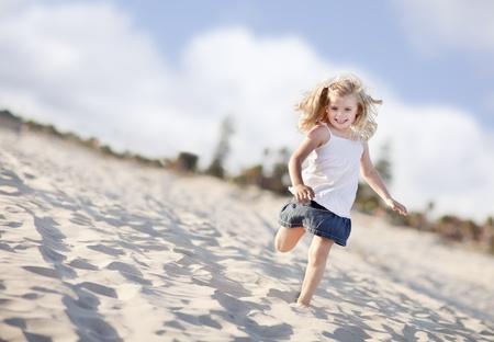 Schattig meisje plezier op het strand een zonnige middag.