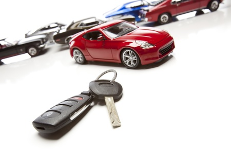 new car lot: Car Keys and Several Sports Cars on White Background. Stock Photo