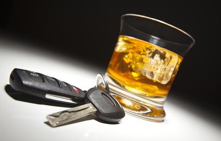 impairment: Alcoholic Drink and Car Keys Under Spot Light. Stock Photo