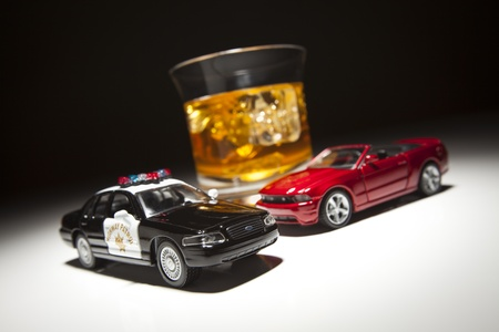 alcohol abuse: Police and Sports Car Next to Alcoholic Drink Under Spot Light.