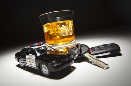 conducci�n: Coche patrulla de carretera junto a la bebida alcoh�lica y claves en lugar de luz. Foto de archivo