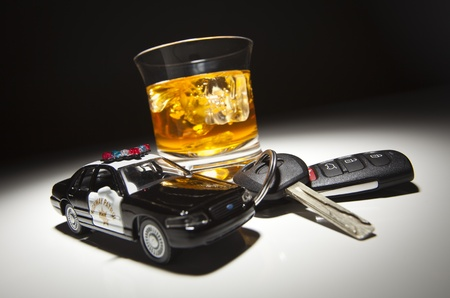 ubriaco: Highway Patrol Police Car accanto alle chiavi sotto luce Spot e bevanda alcolica. Archivio Fotografico
