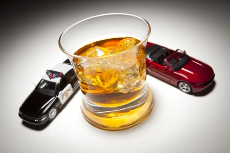 inebriated: Police and Sports Car Next to Alcoholic Drink Under Spot Light.