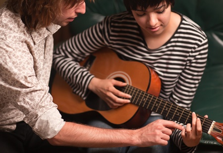 loud music: Young Male Musician Teaches Female Student How To Play the Guitar.