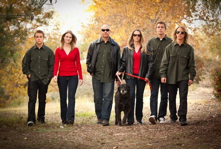 Attractive Family Portrait Walking Outdoors with Their Dog. photo