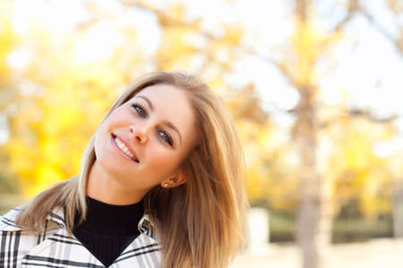 Pretty Young Woman Smiling in the Park on a Fall Day. photo