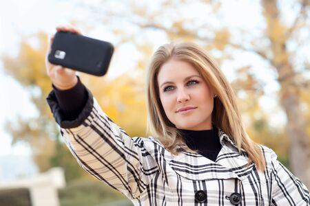 Bella giovane donna scatta foto con la fotocamera del cellulare nel parco una caduta giorno. Archivio Fotografico - 9340416