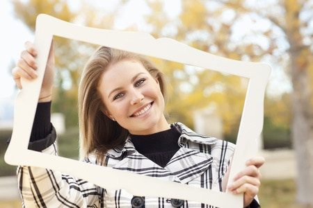 Pretty Young Woman Smiling in the Park on a Fall Day with Picture Frame. Imagens