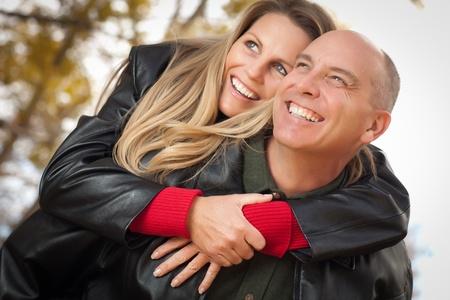 革のジャケットを持つ公園で幸せな、魅力的なカップル。