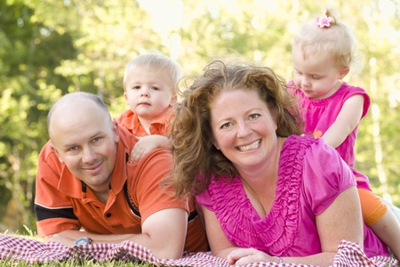 Happy Young Adorable Family with Twins Portrait in the Park. photo