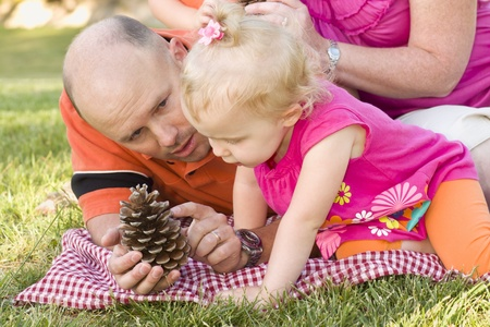 Handsome Father and Adorable Young Daughter Talk about Pine Cone in the Park. photo