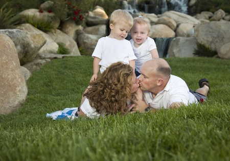 Affectionate Couple Kiss as Adorable Twins Watch in the Park. photo