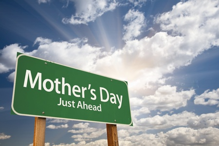 just ahead: Mothers Day Green Road Sign on Dramatic Blue Sky with Clouds.