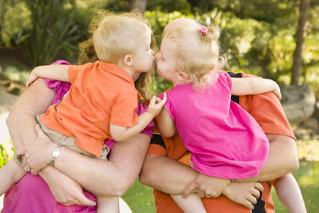 Mom and Dad Holding Kissing Brother and Sister Toddlers in the Park. photo