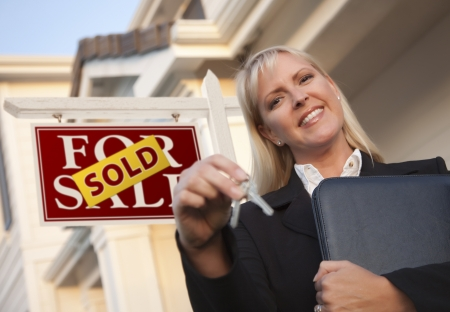 estate: Female Real Estate Agent with Keys in Front of Sold Sign and Beautiful House.