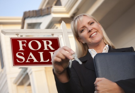 Female Real Estate Agent with Keys in Front of Sign and Beautiful House. Stock Photo