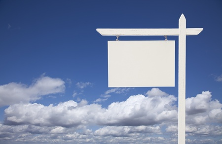 Blank White Real Estate Sign Over Clouds and Sky Ready For Your Own Message. photo