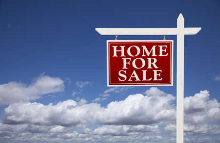 home sale: Red Home for Sale Real Estate Sign Over Beautiful Clouds and Blue Sky.