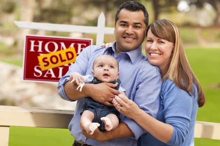 sales person: Happy Mixed Race Couple with Baby in Front of Sold Real Estate Sign. Stock Photo