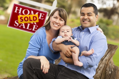 Happy Mixed Race Couple with Baby in Front of Sold Real Estate Sign. Reklamní fotografie