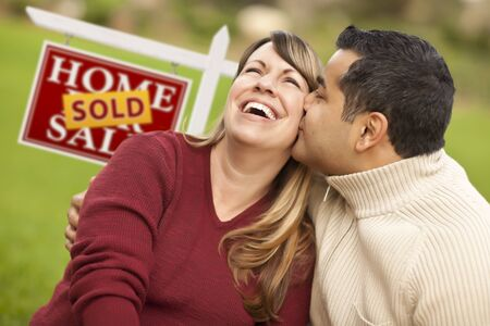 Happy Mixed Race Couple in Front of Sold Real Estate Sign. Stock Photo - 9589917