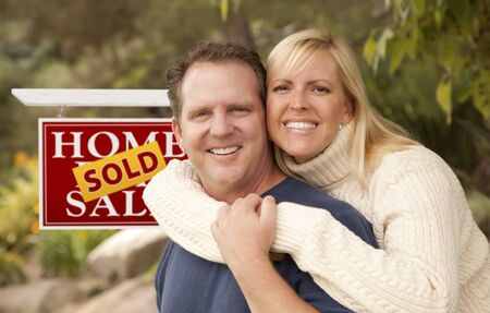 home sale: Happy Attractive Caucasian Couple in Front of Sold Real Estate Sign. Stock Photo