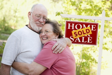 sold: Happy Affectionate Senior Couple Hugging in Front of Sold Real Estate Sign.