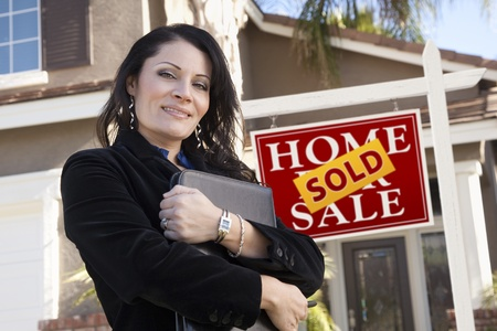 property agent: Proud, Attractive Hispanic Woman in Front of Sold Real Estate Sign and New Home.
