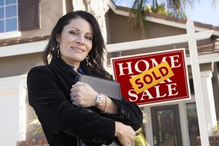 Trots, aantrekkelijke Hispanic vrouw voor verkocht onroerend goed teken en nieuwe huis.
