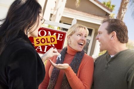 vendiendo: Hispana femenina agente inmobiliario entrega las llaves de casa nuevas par emocionado.