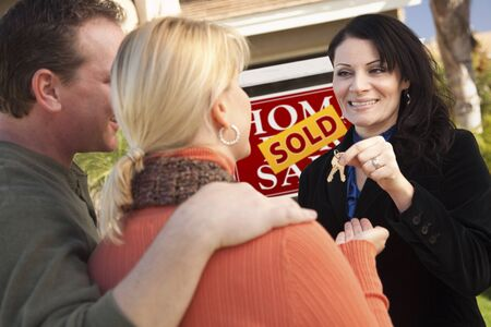 real estate sold: Atractivo hispana femenina agente inmobiliario entrega las llaves de casa nuevas a la feliz pareja. Foto de archivo