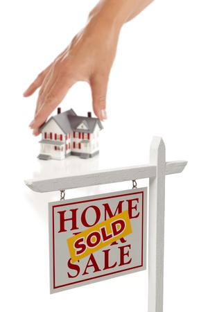 sold small: Womans Hand Choosing Home with Sold Home For Sale Real Estate Sign in Front Isolated on White. Stock Photo