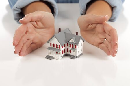 Womans Hands Around Model House on White Surface. photo