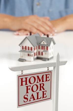 Womans Folded Hands Behind Model House and Home For Sale Real Estate Sign In Front on White Surface. Stock Photo