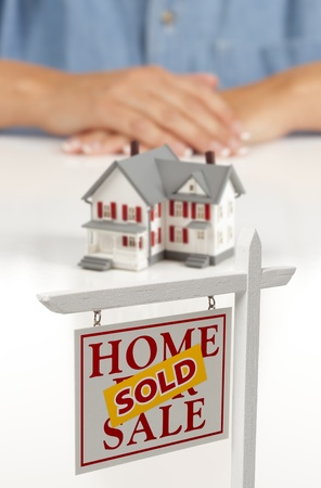 Womans Folded Hands Behind Model House and Sold Home For Sale Real Estate Sign In Front on White Surface. photo