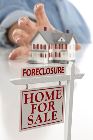 Foreclosure Real Estate Sign in Front of Womans Hand Reaching for Model House on a White Surface. photo