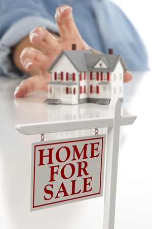 Real Estate Sign in Front of Womans Hand Reaching for Model House on a White Surface.