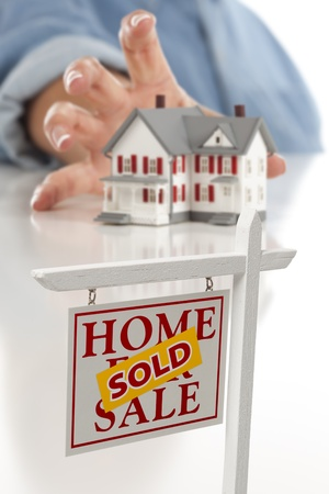 Sold Real Estate Sign in Front of Womans Hand Reaching for Model House on a White Surface.