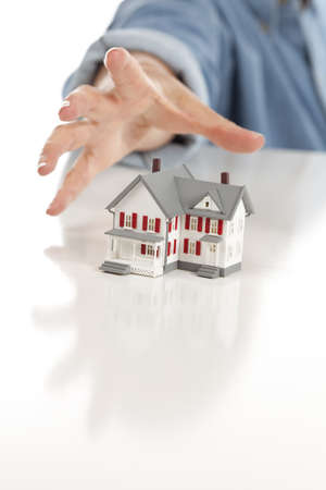 Womans Hand Reaching for Model House on a White Surface. photo