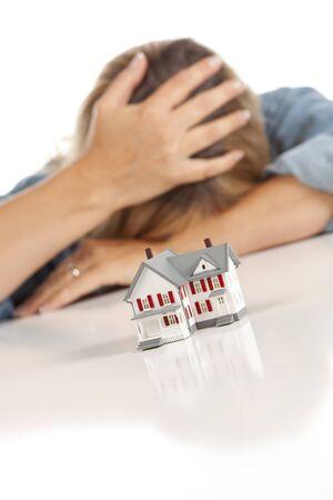 Vrouw met hoofd in Hand achter modelwoning op een witte ondergrond. Stockfoto
