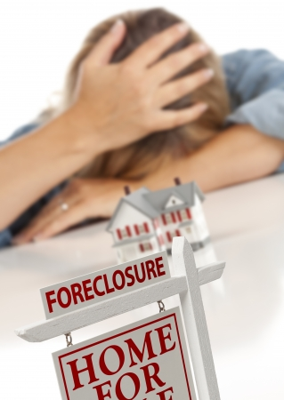 foreclosure: Woman with Head in Hand Behind Model Home and Foreclosure Real Estate Sign in Front.