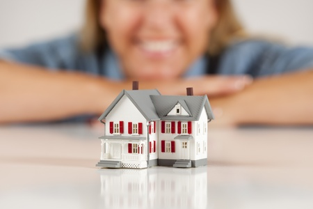 Smiling Woman Leaning on Hands Behind Model House on a White Surface. Archivio Fotografico