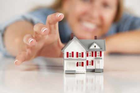 Smiling Woman Reaching for Model House on a White Surface. photo